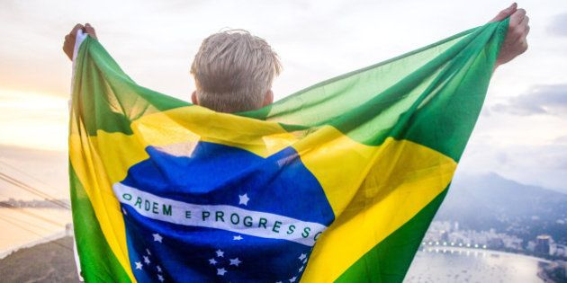 A young man with a colorful brazilian flag around his back at sunset on the top of Sugarloaf mountain...