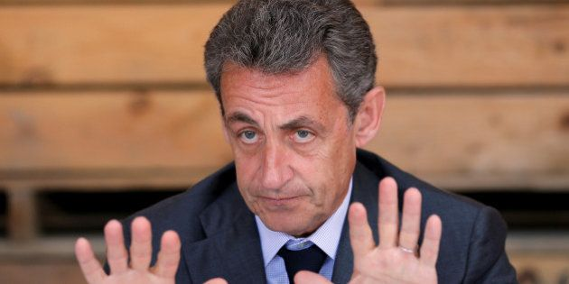 The head of France's Les Republicains political party, former French president Nicolas Sarkozy (C) attends...
