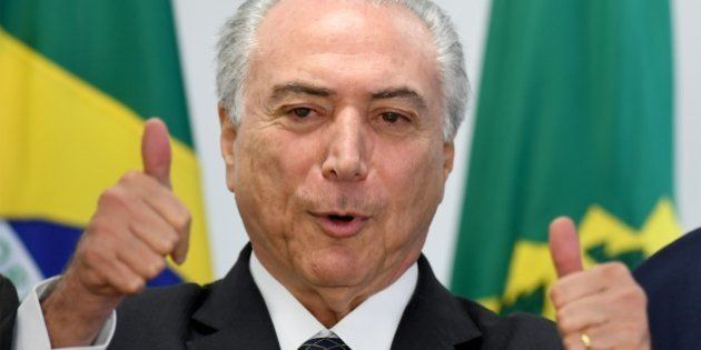 Brazilian acting President Michel Temer gives the thumbs up during a meeting with mayors at the Planalto...