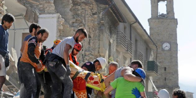 A victim is carried on a stretcher from a collapsed building after an earthquake, in Amatrice, central...