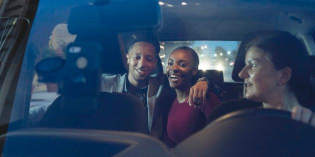 Young couple enjoy a night out using a taxi service booked through an app on their mobile