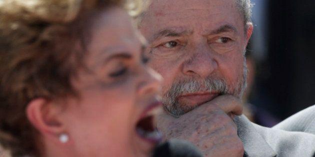 Brazil's former President Luiz Inacio Lula da Silva (R) listens as suspended President Dilma Rousseff...