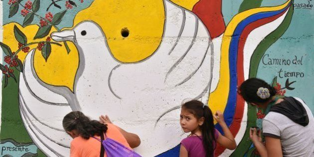 Women and a girl paint a mural alluding to peace on the road leading to Planadas, Tolima department,...
