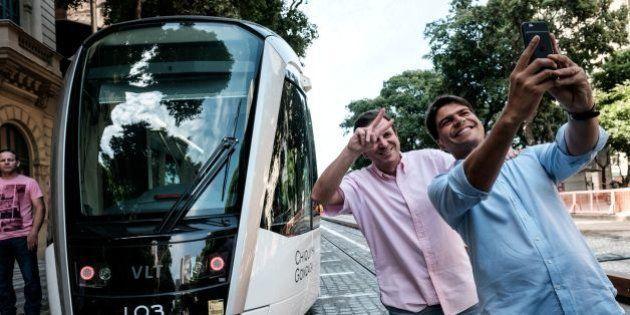 Rio de Janeiro Mayor Eduardo Paes (2nd R) takes pictures with Rio's Municipal Executive Secretary Pedro...