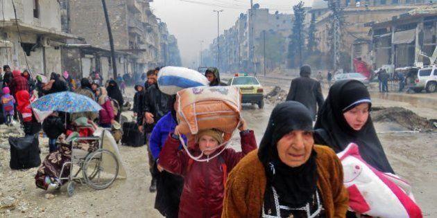 Syrian residents, fleeing violence in the restive Bustan al-Qasr neighbourhood, arrive in Aleppo's Fardos...