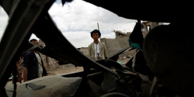 A Yemeni man insepcts a damaged car in Yemen's Huthi rebel-held capital Sanaa on August 29, 2016, after...