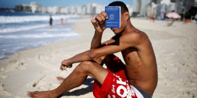 Brazilian unemployed Samuel Matias, 24, shows his Work and Social Security (CTPS) document on Copacabana...