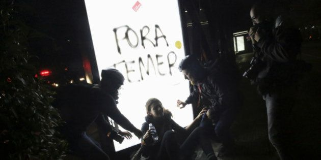 Photographers help a woman who was affected by tear gas during a protest against Brazil's new President...