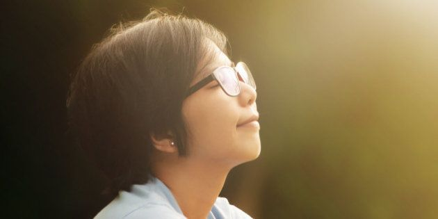 Close up of asian women sitting in a park. Eyeglasses girl deep breath fresh air in the