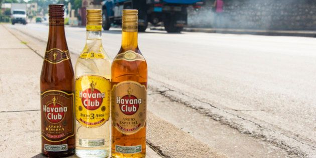 SANCTI SPIRITUS, CUBA - 2015/09/25: El Ron de Cuba: Bottles of Havana Club rum on the pavement with vehicles...