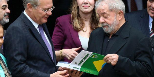 Brazil's former President Luiz Inacio Lula da Silva (R) receives Brazil's Federal Constitution from senator...
