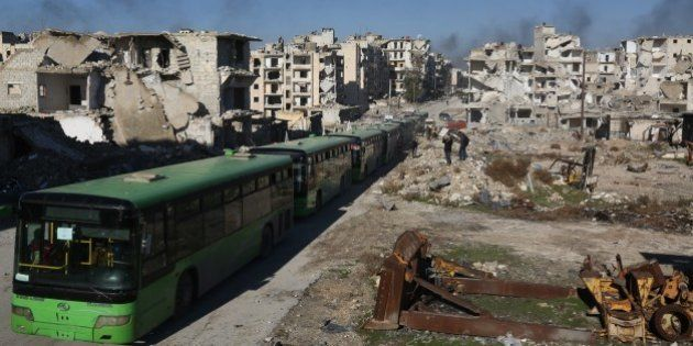 ALEPPO, SYRIA - DECEMBER 15: A convoy including busses and ambulances, wait at a crossing point at Amiriyah...