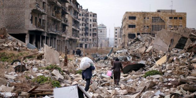 People walk amid the rubble as they carry belongings that they collected from their houses in the government...