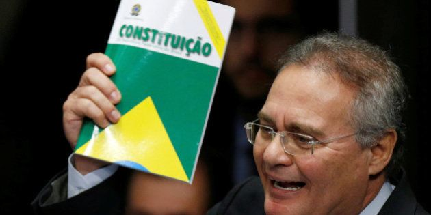Senate President Renan Calheiros holds the Constitution of Brazil as he attends the final session of...