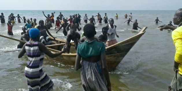 Survivors of a boat accident come back ashore on Lake Albert, on December 26, 2016 in Buliisa, after...