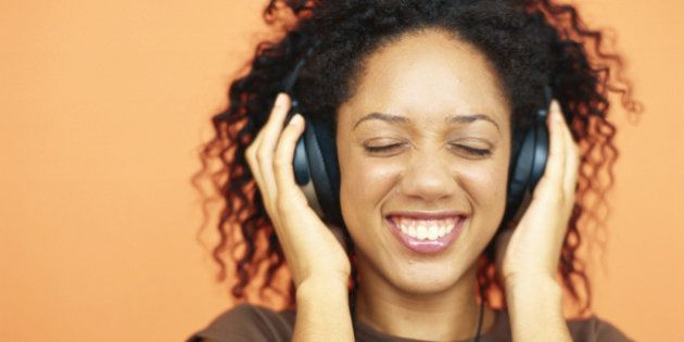 Young woman listening to headphones, smiling,