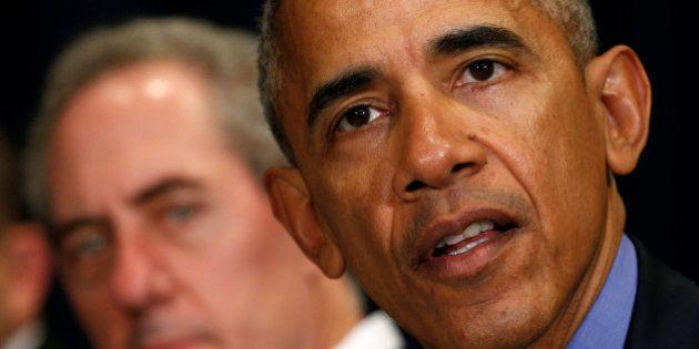 U.S. Trade Representative Michael Froman (L) listens as U.S. President Barack Obama speaks during the...