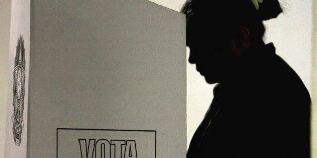 Rio de Janeiro, BRAZIL: A voter digits her ballot at an electronic ballot box at Rocinha's shantytown...