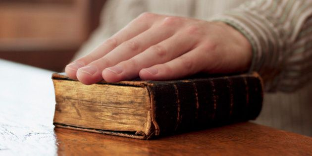 Hand of witness on Bible in