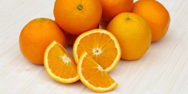 Pile of fresh organic oranges with one cut into half and quarters, on a white wood grained