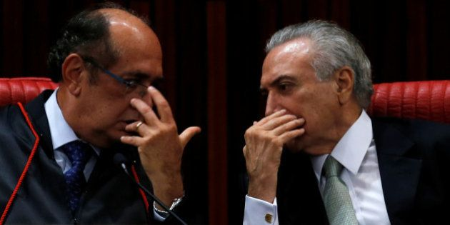 Brazil's interim President Michel Temer (R) speaks with Minister Gilmar Mendes during Mendes' inauguration...
