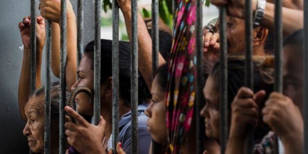 Relatives wait for information following a riot that ended with at least four prisoners killed inside...