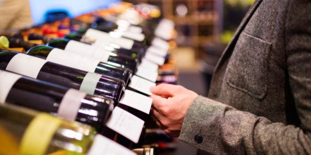 Unrecognizable young man in a wine shop choosing a