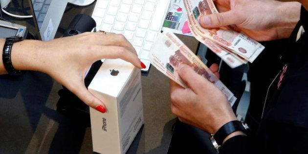 A shop assistant (R) counts Russian rouble banknotes as a customer comes to a store selling Apple products...