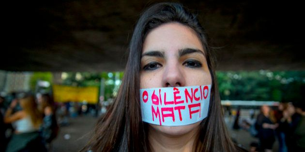 SAO PAULO, BRAZIL - JUNE 08: A woman marchs with a piece of tape over her mouth with a message that reads...
