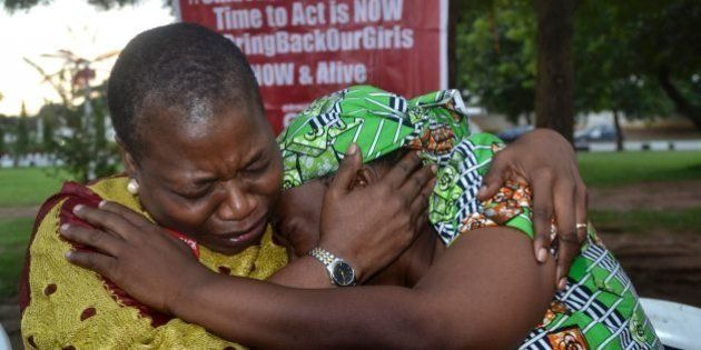 The coordinator of Bring Back our Girls, Prof. Obby Ezekwesili (L), cries while trying to console Esther...