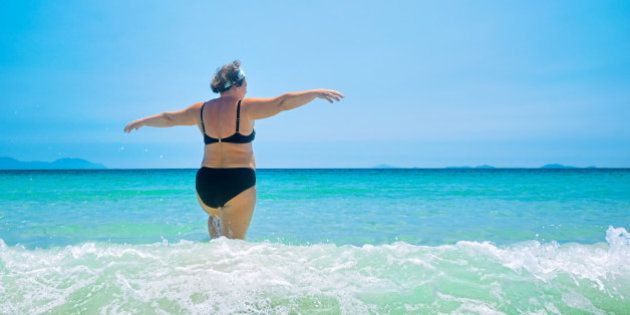 mature woman in swimwear at the sea. Overweight woman in swimsuit comes in water in time of surf, rear view