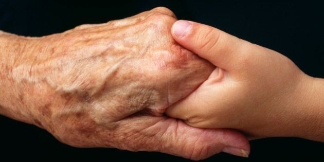 Hands of Old woman and Young girl hold together