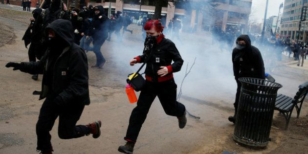 Activists race after being hit by a stun grenade while protesting against U.S. President-elect Donald...