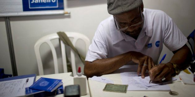 A recruiter looks over paperwork from an applicant at a job fair promoted by the mayor's office to boost...