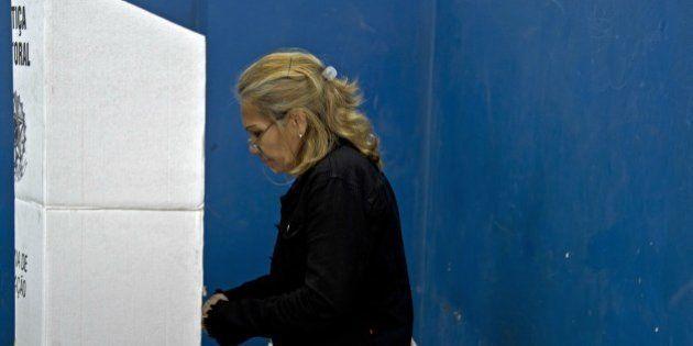 People vote at a polling station inside the Colegio Municipal Ayrton Senna, next to favela da Rocinha...