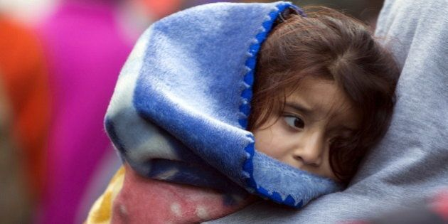 A young asylum seeker rests in the arms of her mother outside the foreign office in Brussels, Belgium...