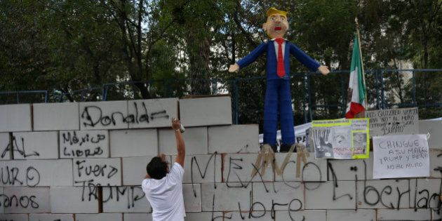 A demonstrator writes on symbolic wall as is seen a pinata representing the U.S. President Donald Trump...