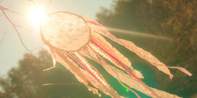 A pinkish dreamcatcher made of lace is blowing in the wind, outdoors, with the sun behind