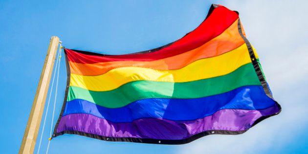 Gay rainbow flags waving over blue sky