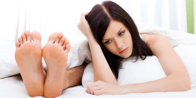 young upset couple lying in a bed, having conflict problem. sad woman face on pillow negative emotions concept and man feet