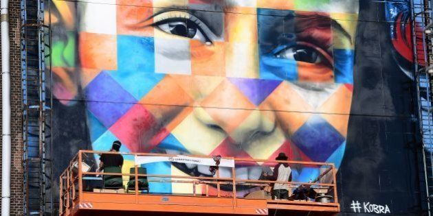 Brazilian street artist Eduardo Kobra (R) and his assistant work on a large graffiti artwork of late...