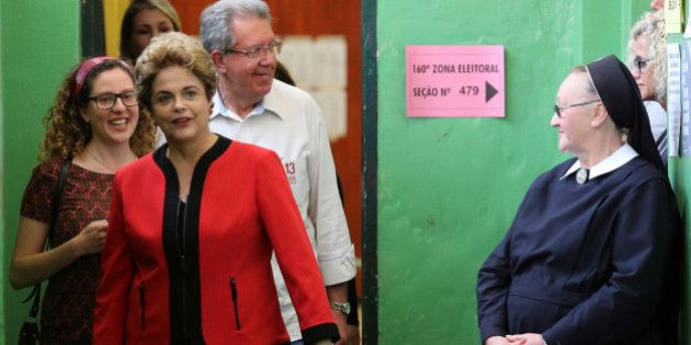 Brazil's former President Dilma Rousseff (in red) arrives to vote during municipal elections in Porto...