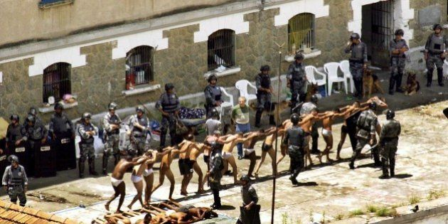 Inmates walk past a gauntlet of riot police as they are rounded-up to be searched in a courtyard of a...