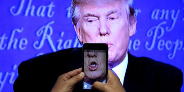 A journalist records a video from screen as Republican U.S. presidential nominee Donald Trump speaks...