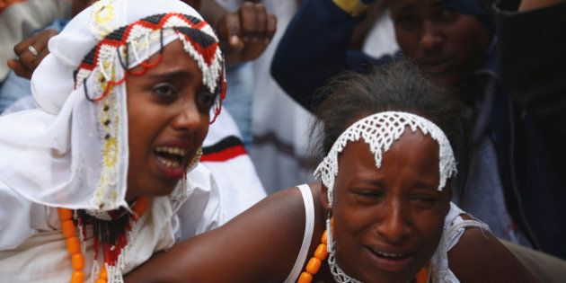 Women react at a protest during Irreecha, the thanksgiving festival of the Oromo people, in Bishoftu...