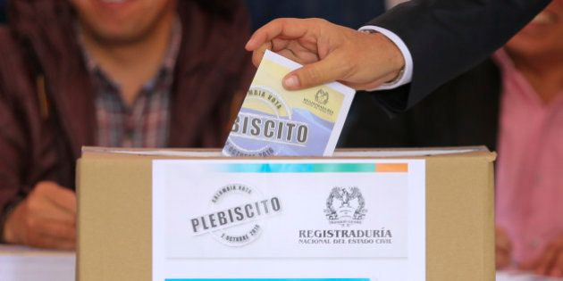A voter casts his ballot in a referendum to decide whether or not to support a peace deal signed between...