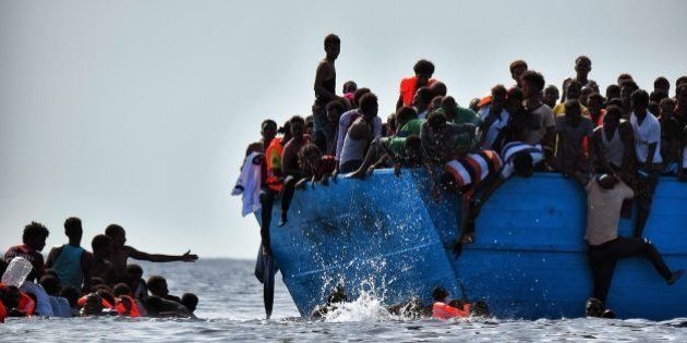 Migrants hang from a boat as they wait to be rescued as they drift in the Mediterranean Sea, some 12...