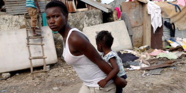 A woman carries a child as they walk in front of destroyed houses after Hurricane Matthew passes Jeremie,...