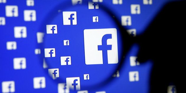 A man poses with a magnifier in front of a Facebook logo on display in this illustration taken in Sarajevo,...