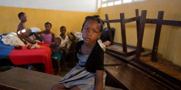 A girl sits on a table in a shelter after Hurricane Matthew passed , in Jeremie, Haiti. Saturday Oct....